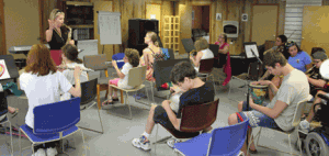Students from music ensemble sit in classroom at Heart Woodlands Music Camp