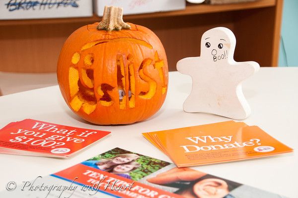 A small pumpkin with the JJ's List logo carved sits on the registration table beside postcards and posters